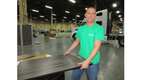 A-volunteer-from-Las-Vegas-Habitat-for-Humanity-stacks-display-materials-donated-by-Surfaces-exhibitors